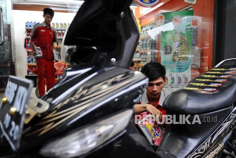 Pekerja sedang menganti oli kendaraan roda dua di gerai Bright Olimart di Jakarta, Rabu (20/7).Republika/Tahta Aidilla