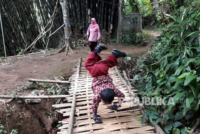 Pelajar Kelas III SDN 10 Cibadak Kabupaten Sukabumi, Mukhlis Abdul Kholik (8 tahaun) berjalan merangkak di sekolahnya, Kamis (8/11).
