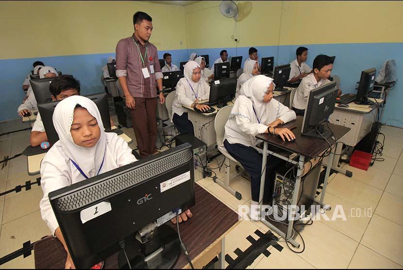 Pelajar menunggu bisa diaksesnya server Ujian Nasional Berbasis Komputer (UNBK) di SMP Muhammadiyah 11 Surabaya, Jawa Timur, Senin (23/4). Sebanyak 46 komputer peserta UNBK di tempat itu tidak dapat mengakses server sejak pukul 07.30 WIB sampai 08.45 WIB.