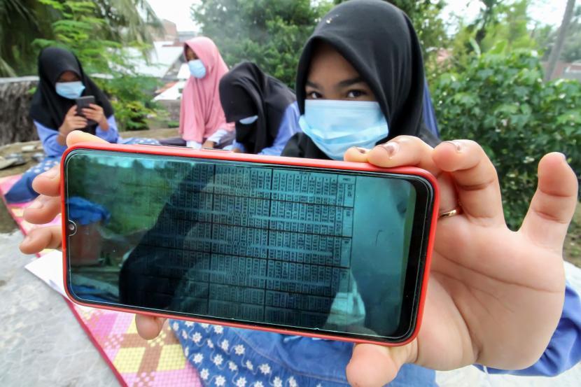 Pelajar menunjukkan bahan pembelajaran dalam jaringan (daring) di atas atap rumah warga di Desa Meuria Paloh, Aceh, Sabtu (31/7/2021). Para pelajar di daerah pedalaman tersebut kesulitan mengikuti proses belajar mengajar secara daring di masa pandemi COVID-19 akibat keterbatasan kuota dan jaringan internet dan terpaksa mencari sinya di ketinggian dan tempat terbuka.