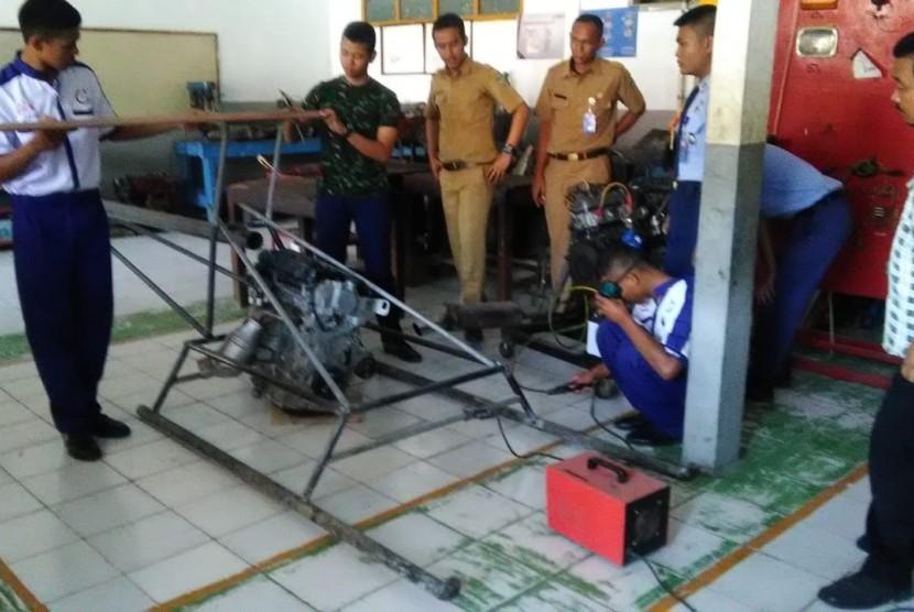 Pelajar SMK Taruna Sakti Purwakarta, sedang merakit helikopter berbahan bakar bensin, Kamis (10/1). Targetnya, dalam empat bulan kedepan helikopter ini akan diujicobakan untuk terbang.
