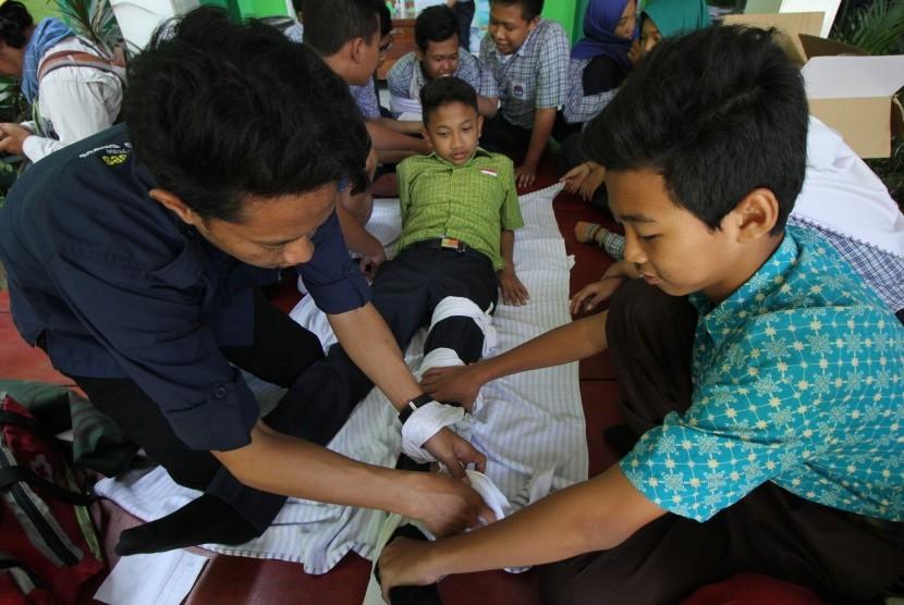 Pelajar SMP Negeri 9 Surabaya mempraktekkan cara memberikan pertolongan pertama gawat darurat (PPGD) kepada korban patah tulang saat pelatihan pembentukan sekolah tanggap bencana di Surabaya, Jawa Timur, Rabu (25/7).