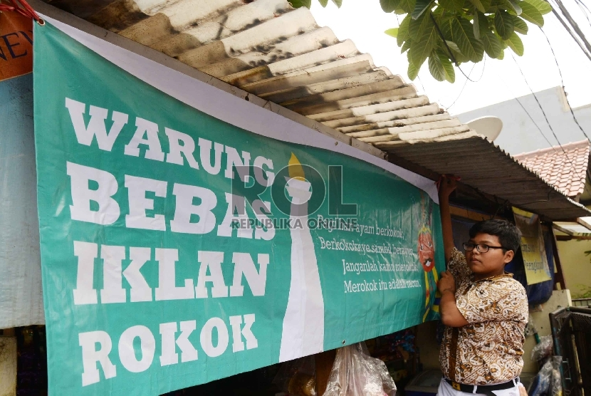 Pelajar SMPN 104 Jakarta menurunkan iklan rokok di warung-warung di dekat sekolah, Jakarta Selatan, Kamis (5/11). (Republika/Yasin Habibi)