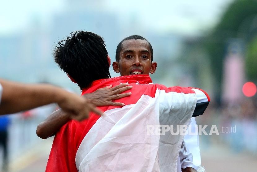 Pelari Indonesia Agus Prayogo berppelukan dengan Pelari Singapura Soh Rui Yong usai memasuki garis finish saat bertanding pada nomor lari marathon SEA Games XXIX Kuala Lumpur di Putrajaya, Malaysia, Sabtu (19/8).