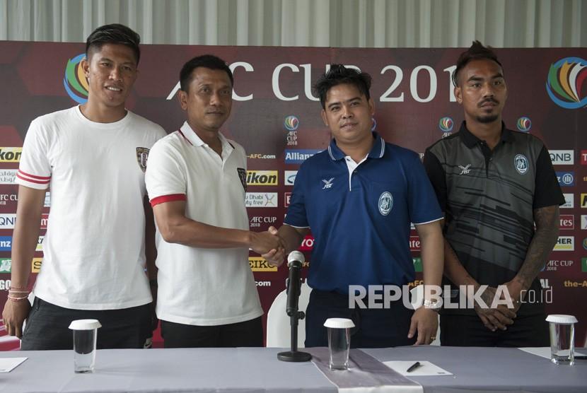 Pelatih Bali United Widodo C Putro (kedua kiri) berjabat tangan dengan Pelatih Yangon United Myanmar Myo Min Tun (kedua kanan) didampingi pesepak bola Yangon United Yan Aung Kyaw (kanan) dan pesepak bola Bali United Agus Nova Wiantara (kiri) seusai konferensi pers menjelang laga Piala AFC 2018 di Sanur, Bali, Senin (12/2).