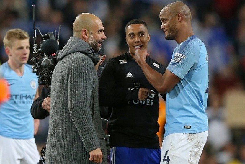 Pelatih Manchester City Pep Guardiola berbicara dengan Vincent Kompany usai pertandingan melawan Leicester, Selasa (7/5) dini hari WIB.