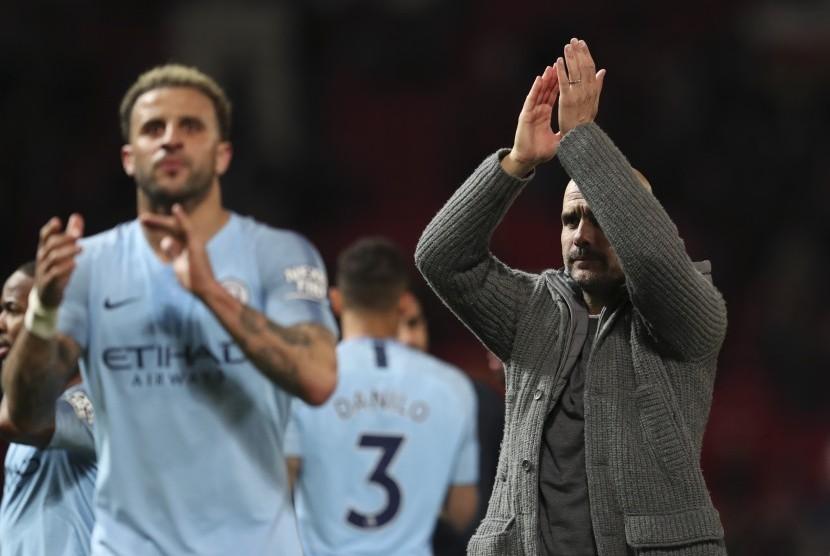 Pelatih Manchester City Pep Guardiola dan anak asuhnya memberi tepuk tangan kepada penggemar seusai timnya memenangkan laga kontra Manchester United dengan skor 2-0 di Old Trafford, Inggris, Rabu (24/4).