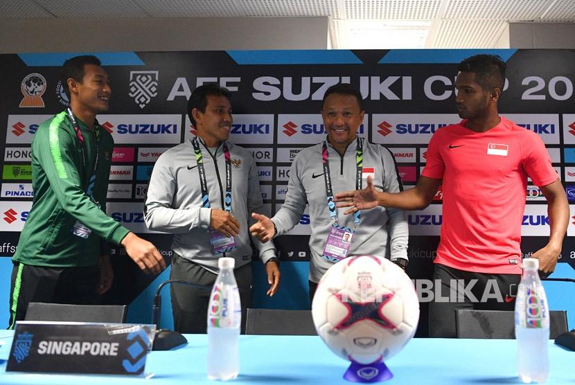 Pelatih timnas Indonesia Bima Sakti (kedua kiri) dan pemain timnas Indonesia Hansamu Yama (kiri) berbincang dengan pelatih timnas Singapura Fandi Ahmad (kedua kanan) serta pemain timnas Singapura Hariss Harun saat konferensi pers piala AFF 2018 di Stadion Nasional, Singapura, Kamis (8/11/2018).
