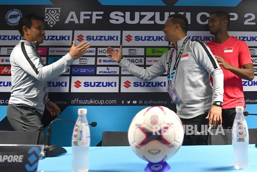 Pelatih timnas Indonesia Bima Sakti (kiri) berbincang dengan pelatih timnas Singapura Fandi Ahmad (tengah) serta pemain timnas Singapura Hariss Harun (kanna) saat konferensi pers piala AFF 2018 di Stadion Nasional, Singapura, Kamis (8/11/2018).