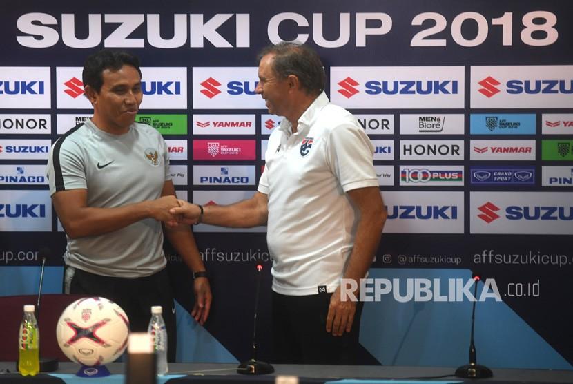 Pelatih timnas Indonesia Bima Sakti (kiri) berjabat tangan dengan Pelatih Thailand Milovan Rajevac (kanan) dalam sesi konferensi pers menjelang laga lanjutan Piala AFF 2018 di Stadion Nasional Rajamangala, Bangkok, Thailand, Jumat (16/11/2018).