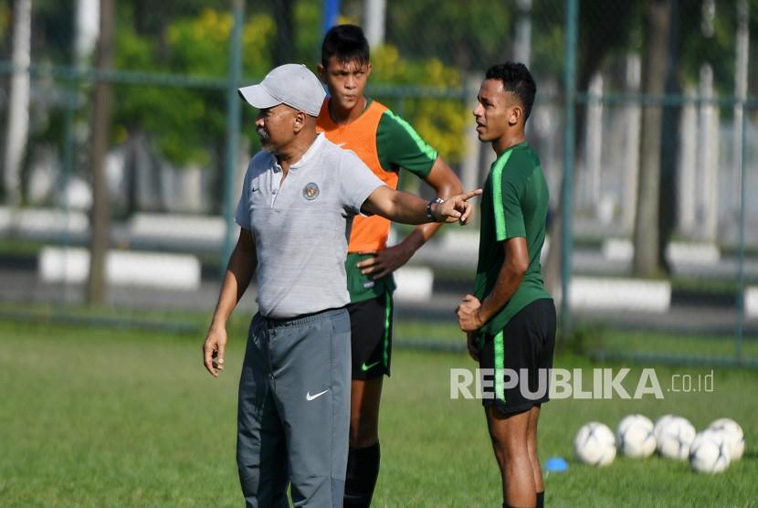 Pelatih Timnas U-18 Fakhri Husaini (kiri) memberikan arahan kepada pemainnya saat latihan di Lapangan Becamex Binh Duong, Vietnam, Selasa (13/8/2019).