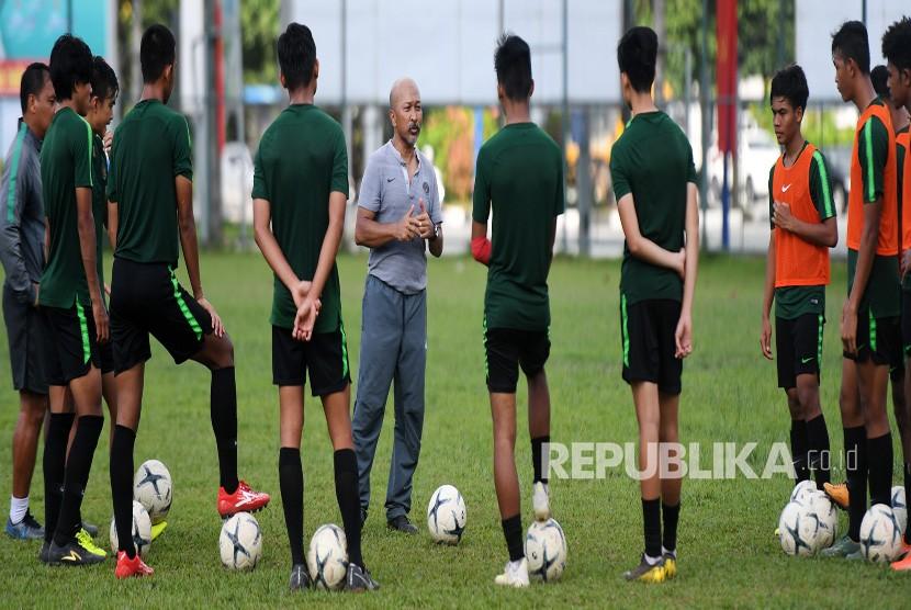 Pelatih Timnas U-18 Fakhri Husaini (tengah) memberikan arahan kepada pemainnya saat latihan di Lapangan Becamex Binh Duong, Vietnam, Kamis (15/8/2019).