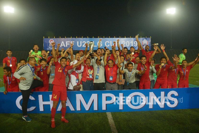Pelatih Timnas U-22 Indra Sjafri (kedelapan kiri) bersama Menteri Pemuda dan Olah Raga Imam Nahrawi (ketujuh kiri) memegang piala beserta pemain dan Ofisial Timnas Indonesia seusai penganugerahan Piala AFF U-22 2019 di Stadion Nasional Olimpiade Phnom Penh, Kamboja