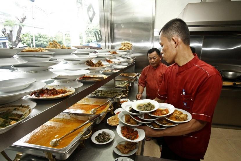 Pelayan bersiap menyajikan beragam makanan di sebuah rumah makan Padang.