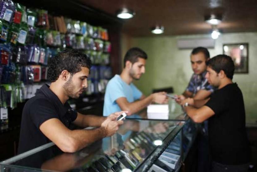 Pelayan toko tengah melayani pembeli iPhone 5 di sebuah gerai telepon seluler di Gaza, Palestina, Selasa (16/10).