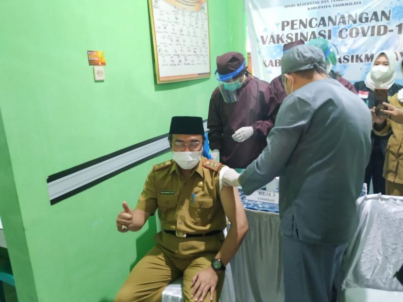 Peluncuran program vaksinasi Covid-19 di Kabupaten Tasikmalaya dilakukan di Puskesmas Tinewati, Kecamatan Singaparna, Senin (1/1). Sekda Kabupaten Tasikmalaya Muhammad Zen menjadi orang pertama yang menerima vaksinasi di Kabupaten Tasikmalaya.