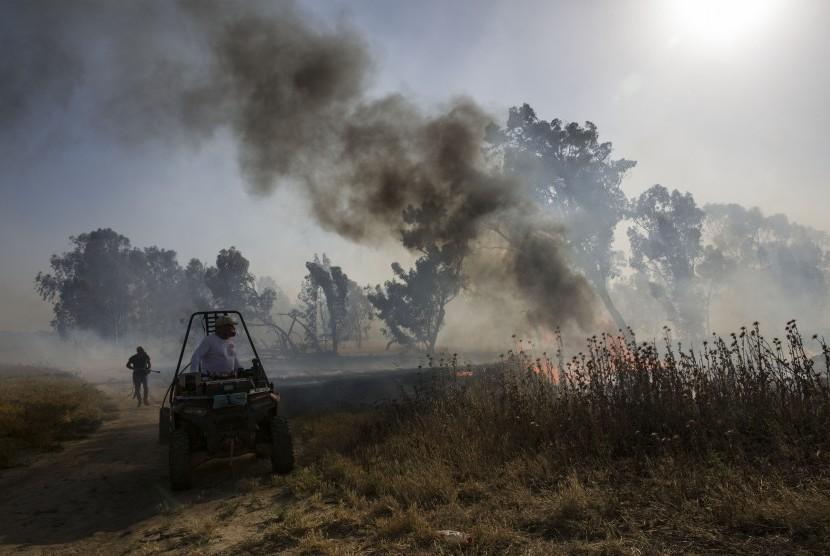 Pemadam kebakaran Israel memadamkan api yang berasal dari alat pembakar yang diluncurkan dari Jalur Gaza, dekat pagar perbatasan Israel dan Gaza, Rabu, (15/5). Rakyat Palestina menandai peringatan Hari Nakba ke-71 dengan berdemonstrasi di Tepi Barat yang diduduki Israel dan Jalur Gaza.