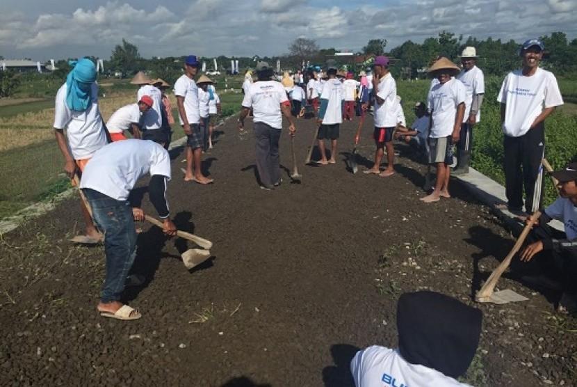 Pemadatan jalan salah satu program CSR yang dilaksanakna BRI Peduli Lingkungan di Kabupaten Klaten, Jawa Tengah, Sabtu (24/3).
