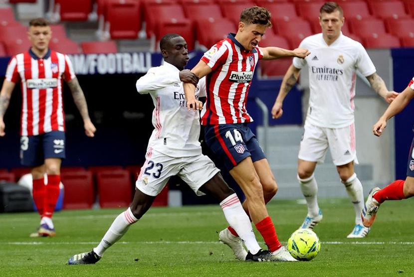 Pemain Atletico Madrid Marcos Llorente berebut bola dengan pemain Real Madrid Ferland Mendy dalam Derbi Madrid di Stadion  Wanda Metropolitano Ahad (7/3).