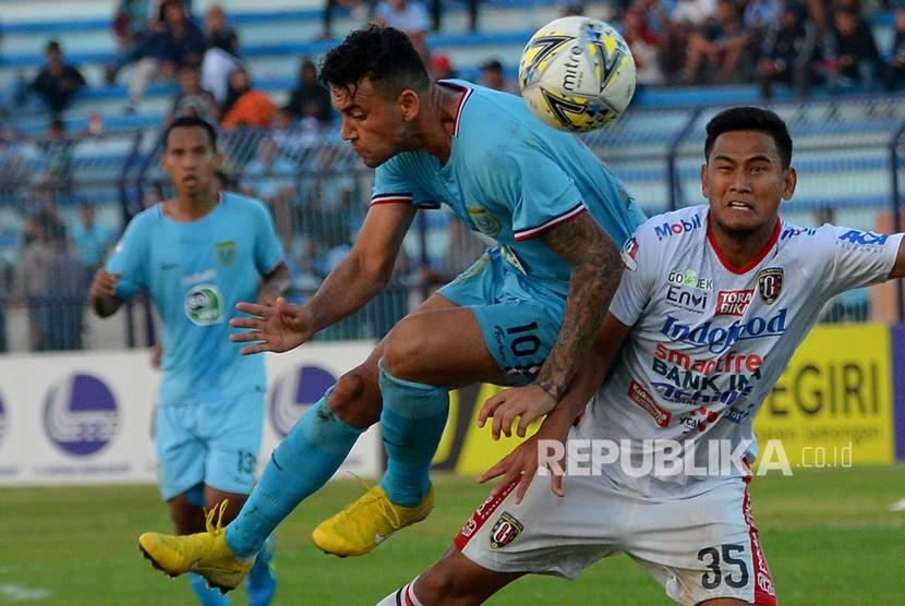 Pemain Bali United Haudi Abdillah (kanan) berebut bola dengan pemain Persela Lamongan Alex Dos Santos Goncalves (kedua kanan) dalam pertandingan lanjutan Liga 1 2019 di Stadion Surajaya Lamongan, Jawa Timur, Kamis (18/7/2019).