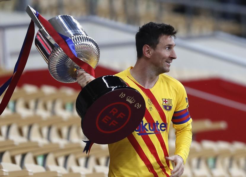Pemain Barcelona Lionel Messi memegang trofi setelah memenangkan final Copa del Rey Spanyol 2021 melawan Athletic Bilbao di stadion La Cartuja di Seville, Spanyol, Sabtu 17 April 2021.