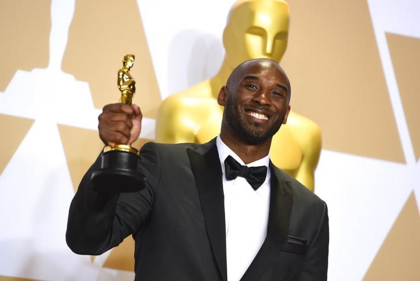 Pemain basket Kobe Bryant memegang piala Oscar sebagai pemenang kategori film pendek animasi Dear Basketball, di Los Angeles, Senin (5/3).