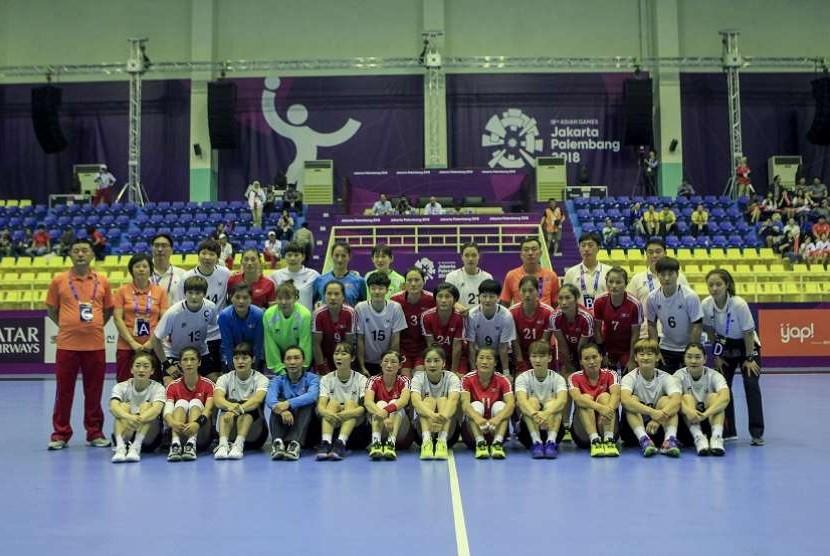 Pemain dan official bola tangan putri Korea Utara, dan Korea Selatan, foto bersama sebelum pertandingan babak penyisihan grup A di GOR POPKI, Cibubur, Jakarta, Selasa (14/8).