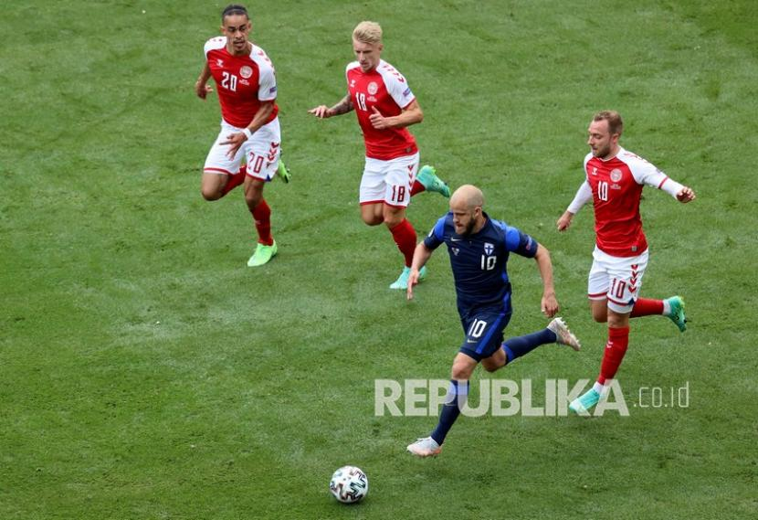 Pemain FinlandiaTeemu Pukki (bawah) mengontrol bola saat pemain Denmark Yussuf Poulsen (kiri) Daniel Wass (tengah) dan Christian Eriksen berlari untuk menghentikannya pada pertandingan grup B kejuaraan sepak bola Euro 2020 antara Denmark dan Finlandia di stadion Parken di Kopenhagen, Denmark, Sabtu (12/6).