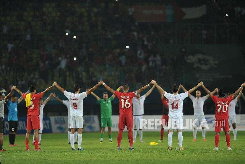 Pemain Indonesia dan pemain Palestina memberikan salam hormat kepada para suporter seusai pertandingan penyisihan Grup A cabang olahraga sepak bola Asian Games 2018 di Stadion Patriot, Bekasi,