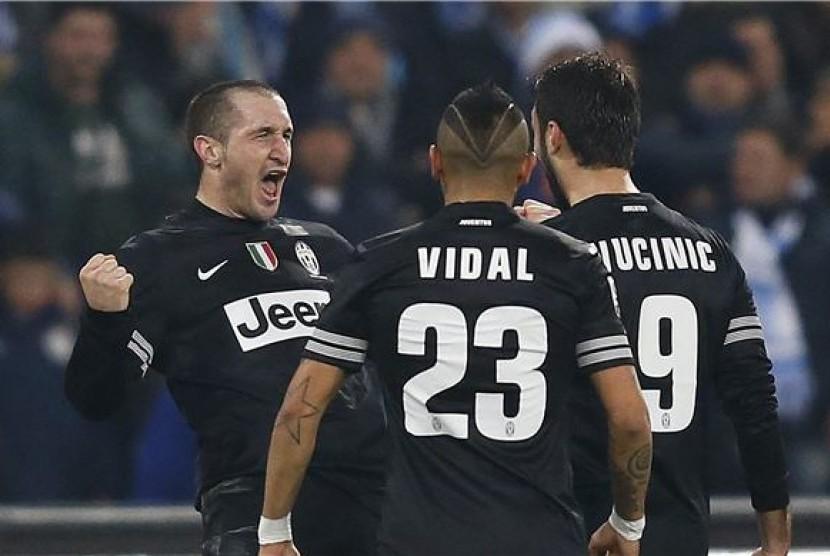 Pemain Juventus, Giorgio Chiellini (kiri), melakukan selebrasi saat menghadapi Napoli di laga Seri A Italia di San Paolo, Napoli, Jumat (1/3).