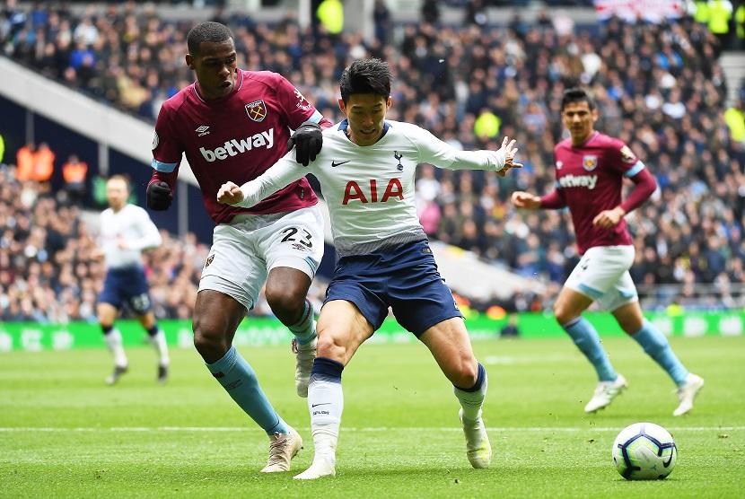 Pemain Klub West Ham, Issa Diop (kiri) sedang berebut bola dengan pemain Tottenham Hotspur Son Heung Min (tengah).