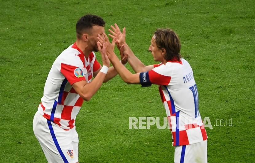 Pemain Kroasia Ivan Perisic (kiri) merayakan dengan Luka Modric setelah mencetak gol ketiga timnya pada pertandingan grup D kejuaraan sepak bola Euro 2020 antara Skotlandia dan Kroasia di Stadion Hampden Park di Glasgow,  Rabu (23/6) dini hari WIB.