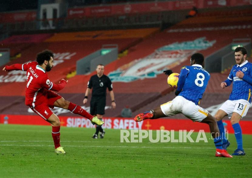 Pemain Liverpool Mohamed Salah (kiri) menembak bola pada pertandingan sepak bola Liga Utama Inggris antara Liverpool FC dan Brighton Hove Albion di Liverpool, Kamis (4/2) dini hari WIB.