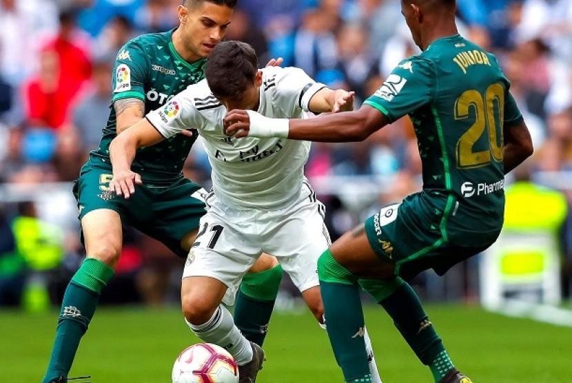Pemain Madrid berebut bola dengan pemain Real Betis dalam pertandingan di Santiago Bernabeu, Ahad (20/5).