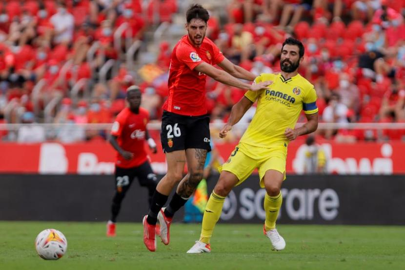 Pemain Mallorca Fer Nino (merah) berebut bola dengan pemain Villarreal Raul Albiol di La Liga Spanyol.
