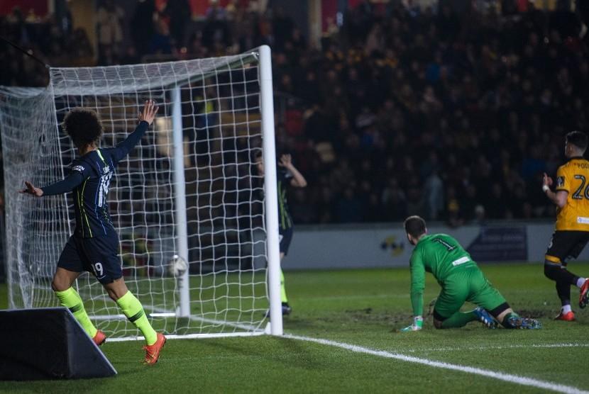 Pemain Manchester City Leroy Sane (kiri) merayakan keberhasilan mencetak gol pertama pada pertandingan putaran kelima Piala FA antara Newport County dan Manchester City di Rodney Parade di Newport, Inggris, Sabtu (16/2).