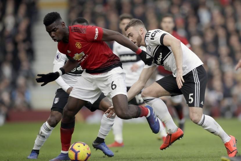 Pemain Manchester United, Paul Pogba (kiri), berebut bola dengan pemain Fulham, Calum Chambers, dalam laga Liga Inggris di stadion Craven Cottage, London, Sabtu.