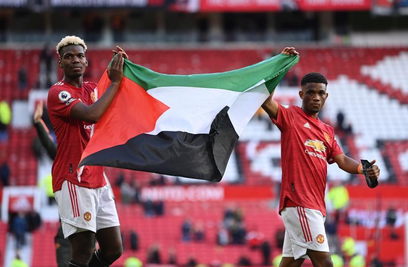 Pemain Manchester United Paul Pogba (kiri) dan Amad (kanan) mengibarkan bendera Palestina ketika menyampa suporter setelah pertandingan sepak bola Liga Primer Inggris antara Manchester United dan Fulham FC di Manchester, Inggris, 18 Mei 2021.