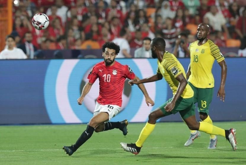Pemain Mesir Mohamed Salah mencoba melewati pemain Afrika Selatan dalam pertandingan babak 16 besar Piala Afrika 2019, Ahad (7/7) dini hari.