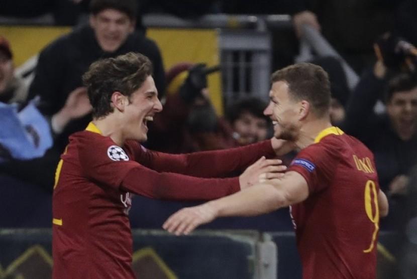 Pemain muda AS Roma Nicolo Zaniolo (kiri) merayakan golnya ke gawang Porto bersama rekannya Edin Dzeko.