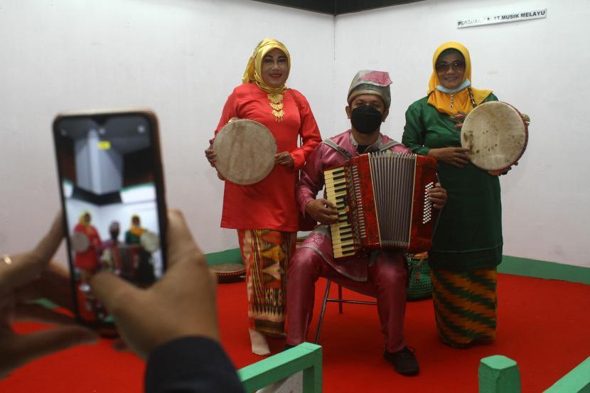 Pemain musik akordeon Syahroni (tengah) berfoto bersama dua pengunjung saat pameran temporer alat musik tradisional di Pontianak, Kalimantan Barat, Senin (20/9/2021). Pameran yang digelar UPT Museum Kalbar tersebut menampilkan 70 alat musik tradisional khas Suku Dayak dan Melayu dari Kalbar.