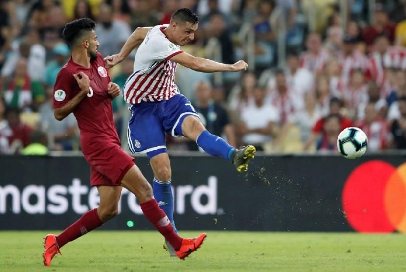 Pemain Paraguay Oscar Cardozo menendang bola dijaga pemain Qatar Tarek Salman pada laga Grup B Copa America 2019 di Stadion Maracana, Rio de Janeiro, Brasil, Senin (17/6) dini hari WIB.