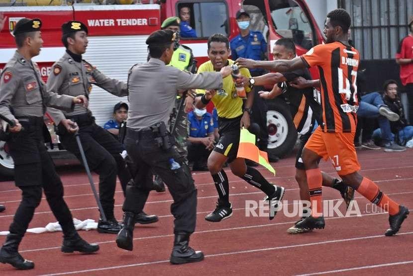 Pemain Perseru Serui Dony Harold Monim (kanan) mengejar asisten wasit Tri Wahyudi (ketiga kanan) untuk memprotes keras dalam pertandingan melawan PSIS Semarang saat pertandingan lanjutan Liga 1 Indonesia di Stadion Moch. Soebroto, Magelang, Jawa Tengah, Ahad (23/9).