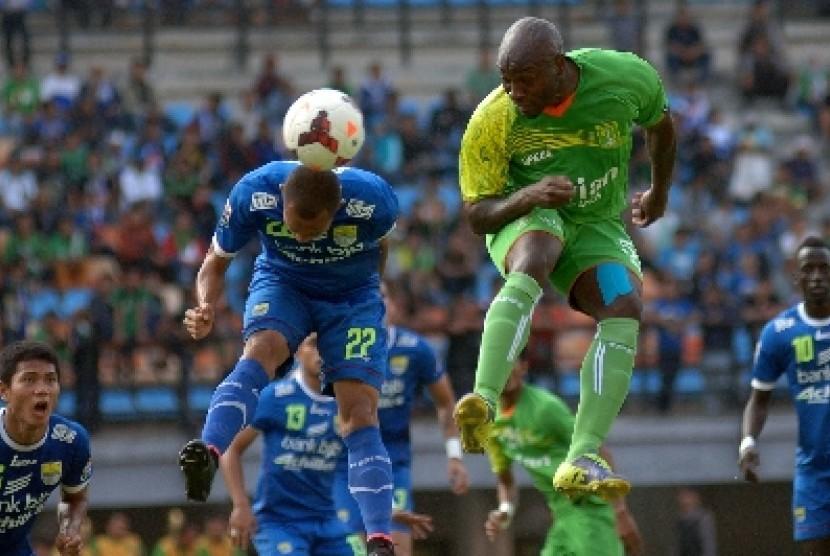 Pemain Persib Bandung, Supardi Nasir (kiri) duel udara dengan penggawa Persebaya Surabaya, Emmanuel Kenmogne.