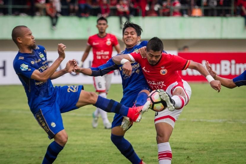 Pemain Persija Jakarta Bambang Pamungkas (kanan) menendang bola namun dihadang pemain Persib Bandung Supardi (kiri) dan Purwaka Yudi (dua kiri) pada pertandingan Liga I Gojek Traveloka di Stadion Manahan, Solo, Jawa Tengah, Jumat (3/11).