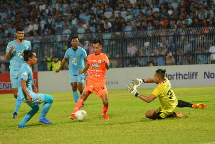 Pemain Persija Jakarta Novri Setiawan (kedua kanan) berusaha melewati pemain Persela Lamongan Samsul Arifin (kiri) dan penjaga gawang Dwi Kuswanto (kanan) dalam pertandingan Liga 1 2019 di Stadion Surajaya Lamongan, Jawa Timur, Sabtu (22/6).
