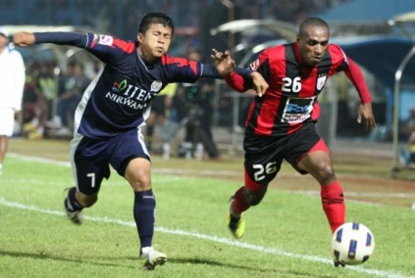 Pemain Persipura Jayapura, Ortizan Salosa (kanan) dalam pertandingan kompetisi Indonesia Super League (ISL) di stadion Kanjuruhan, Malang, Jawa Timur.