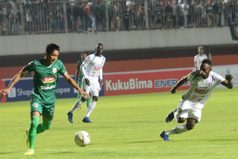 Pemain PSS Sleman, Purwaka Yudi dibayangi pemain Arema Riky Kayame pada pertandingan perdana Liga 1 di Stadion Maguwoharjo, Sleman, DIY, Rabu (15/5).