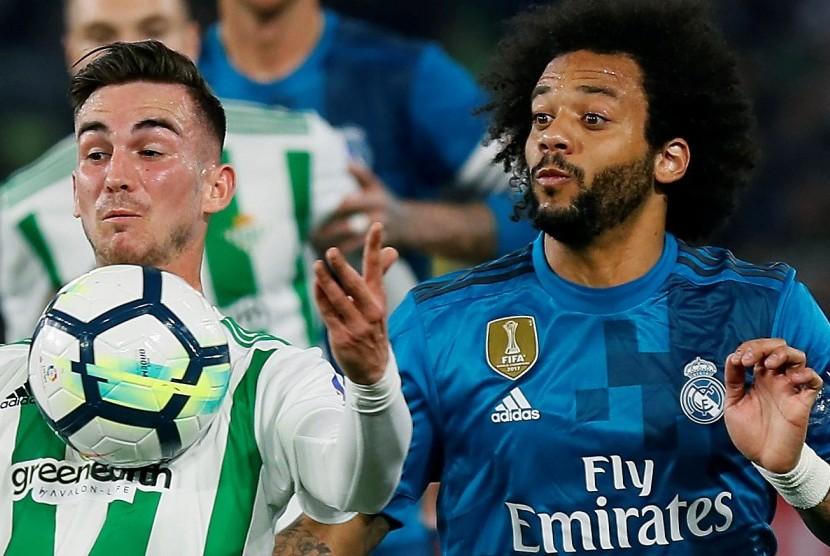 Pemain Real Betis, Fabian Ruiz (kiri), berebut bola dengan bek Real Madrid, Marcelo, pada laga La Liga di Benito Villamarin, Senin (19/2) dini hari WIB.