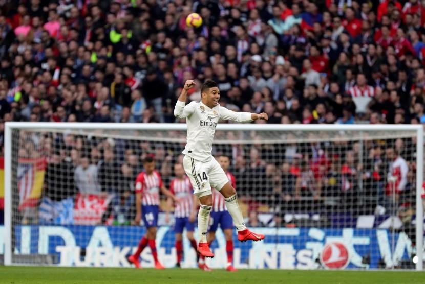 Pemain Real Madrid Carlos Henrique Casimiro (tengah) beraksi saat duel kontra Atletico Madrid, Sabtu (9/2). Casemiro menyumbang satu gol.